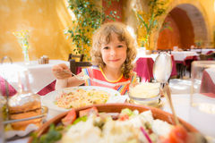 Child eating in summer cafe Stock Images