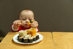 Child eating sushi at home, cute baby royalty free stock image