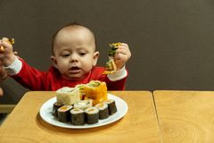 Child eating sushi at home, cute baby stock image