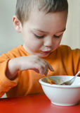 Child eating. Child toddler eating pasta from a bowl at table royalty free stock images