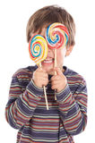 Child eating two lollipops Stock Image