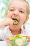 Child eating vegetable salad Stock Images