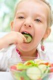 Child eating vegetable salad Stock Images