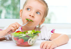 Child eating vegetable salad Stock Photos