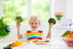 Baby eating vegetables. Solid food for infant. Child eating vegetables sitting in white high chair. Solid food for baby. Little boy eating healthy vegetable royalty free stock photos