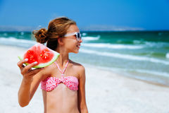 Child eating watermelon on the beach Stock Image