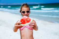 Child eating watermelon on the beach Stock Photos
