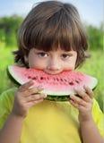 Child eating watermelon in the garden Stock Photos