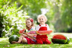 Kids eating watermelon in the garden Stock Photo