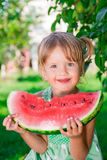 Child eating watermelon on the park in summer time. . Enjoy. Portrait.  Happy girl. Stock Photo