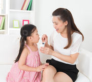 Child eating yoghurt. Eating yogurt. Happy Asian family eating yoghurt at home. Beautiful mother  feeding child, healthcare concept Stock Image