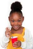Child Eating Yogurt. Happy little girl eating yogurt Stock Image
