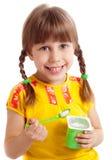 Child eating yogurt. Little child eating yogurt, white background Royalty Free Stock Photo