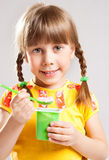Child eating yogurt. Little girl eating yogurt with a spoon Royalty Free Stock Images