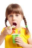 Child eating yogurt. Little child eating yogurt, on white background Royalty Free Stock Image