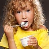 Child eating yogurt. Little happy child eating yogurt Royalty Free Stock Images