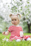 Child eating yogurt. In a spring floral park Stock Image