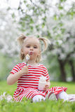 Child eating yogurt. In a spring floral park Royalty Free Stock Image