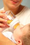 Child eats from bottle Royalty Free Stock Photography