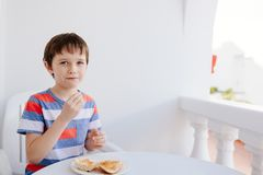 Child eats a bread roll with jam for breakfast Royalty Free Stock Images