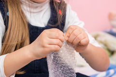 The child eats bubbles on packaging bag Royalty Free Stock Photos