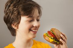 Child eats burger on grey background. Male child with hamburger stock photo