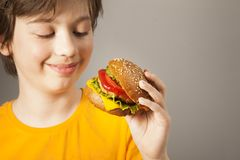 Child eats burger on grey background. Male child with hamburger royalty free stock photography