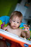 Child eats cake in the highchair Stock Photography