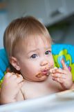 Child eats cake in the highchair Royalty Free Stock Photography