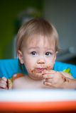 Child eats cake in the highchair Royalty Free Stock Photos