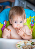 Child eats cake in the highchair Stock Image
