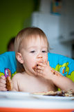 Child eats cake in the highchair Stock Photos