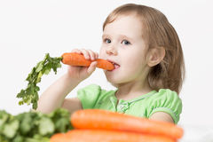 Child eats a carrot. Healthy Eating Stock Photo