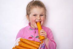 The child eats carrots. A source of vitamins and microcells necessary for health Stock Images