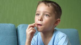 The child eats chips. Child puts potato chips in his mouth. Portrait of a child in a room chewing chips. The impact of