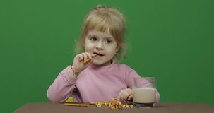 The child eats cookies. A little girl is eating cookies sitting on the table. stock photo