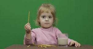The child eats cookies. A little girl is eating cookies sitting on the table. stock photos