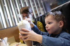 Child eats foam of milkshake Royalty Free Stock Photos