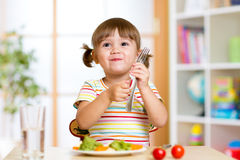 Child eats healthy food at home or kindergarten Stock Images