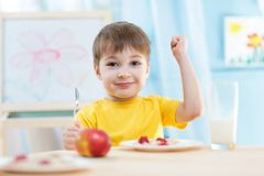 Child eats healthy food showing his strength. Child boy eats healthy food showing his strength indoors stock photo