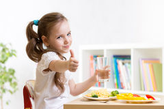Child eats healthy food showing thumb up. Child girl eats healthy food showing thumb up Stock Images
