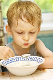 Child eats hot porridge Royalty Free Stock Photos