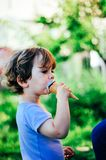 Child eats ice cream on a summer day in the shade of a tree. In the garden Stock Images