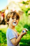 Child eats ice cream on a summer day in the shade of a tree. In the garden Royalty Free Stock Photo