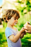 Child eats ice cream on a summer day in the shade of a tree. In the garden Royalty Free Stock Photography