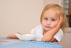Child eats in the kitchen Royalty Free Stock Images