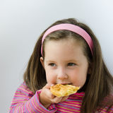 Child eats a pancake. Pretty little girl eats a pancake for breakfast Royalty Free Stock Photography