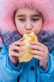 The child eats a pancake. A child eats a pancake, on holiday , seeing the Russian winter Royalty Free Stock Photos