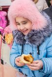 The child eats a pancake. A child eats a pancake, on holiday , seeing the Russian winter Royalty Free Stock Photo