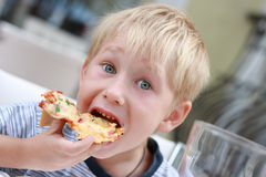 Child eats pizza. Royalty Free Stock Photo